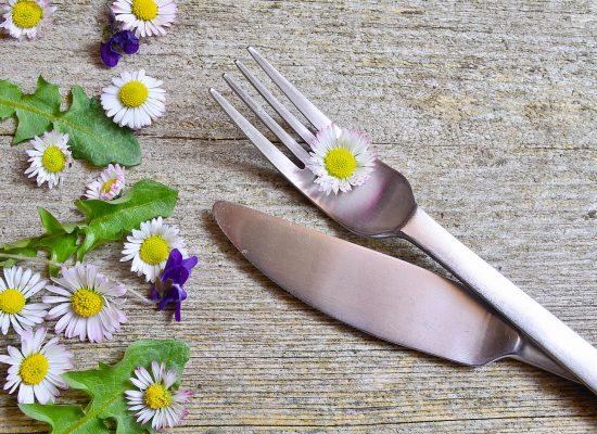 Blumen auf einer Gabel auf Holzhintergrund